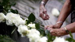 Family members of those killed in the 9/11 attacks lay flowers and press pennies into a memorial before a 9/11 wreath-laying ceremony at Boston Public Garden in 2018.