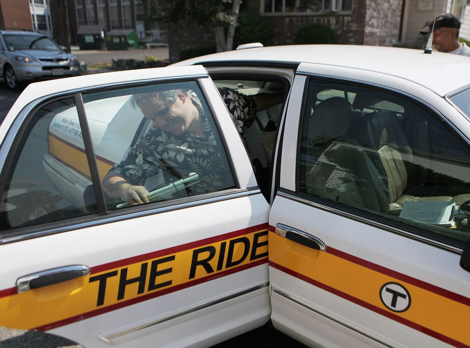 A passenger leaves a vehicle used by the MBTA's The Ride service.