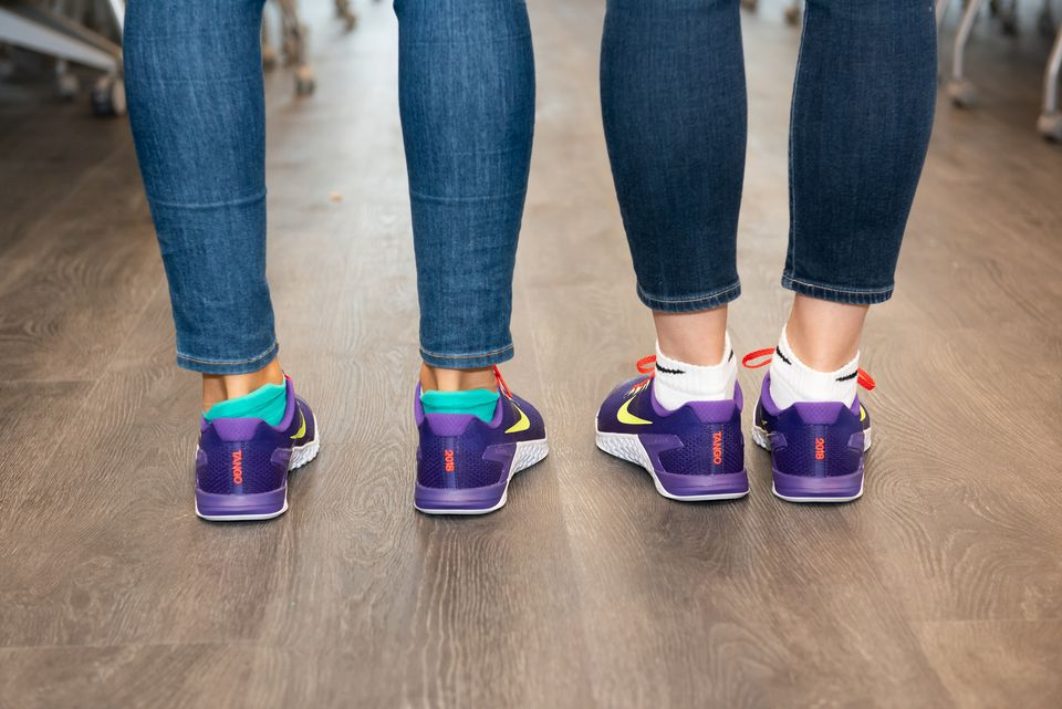 Two Tango employees wearing shoes given this year to workers to mark the company's move to its new space at 100 Binney St.