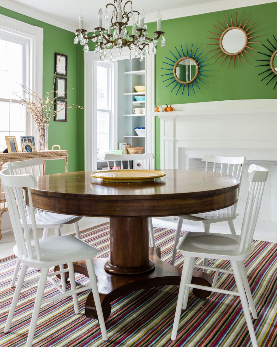 The dining room table, paired with Serena & Lily chairs, was a flea-market find that Bourque had refinished. The indoor/outdoor rug is by Dash & Albert, the mirrors are from Pottery Barn, and the chandelier is vintage.