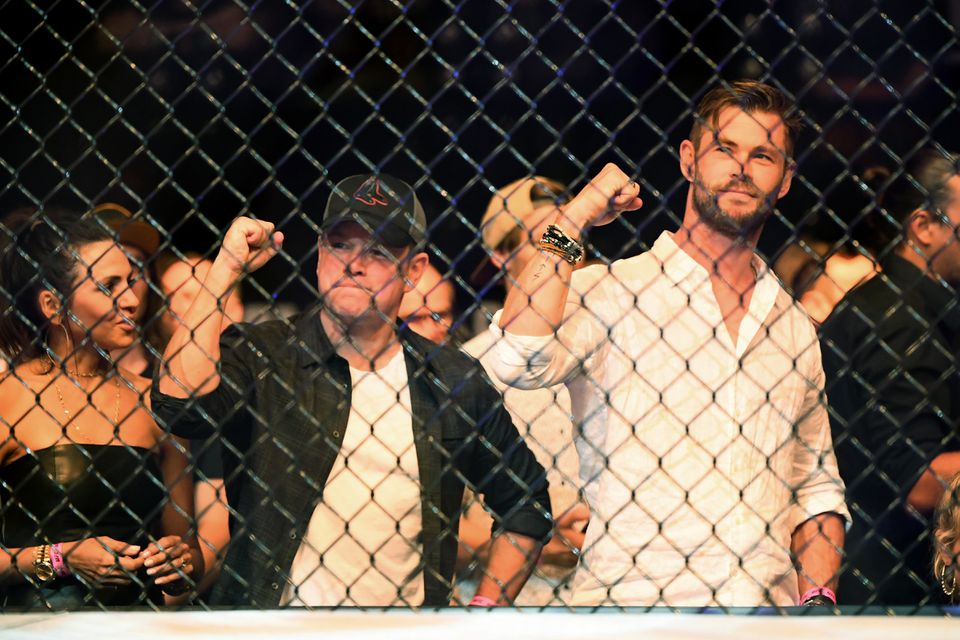 Matt Damon and Chris Hemsworth sit ringside during UFC234 at Rod Laver Arena on Feb. 10, 2019 in Melbourne, Australia. Damon's wife, Luciana Barroso, is pictured at far left.