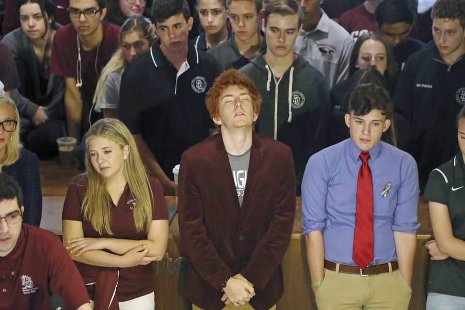 Jaclyn Corin, Ryan Deitsch and Alfonso Calderon along with their classmates from Marjory Stoneman Douglas High School listen as fellow student Lorenzo Prado speaks at a news conference recalling the day of the shooting.
