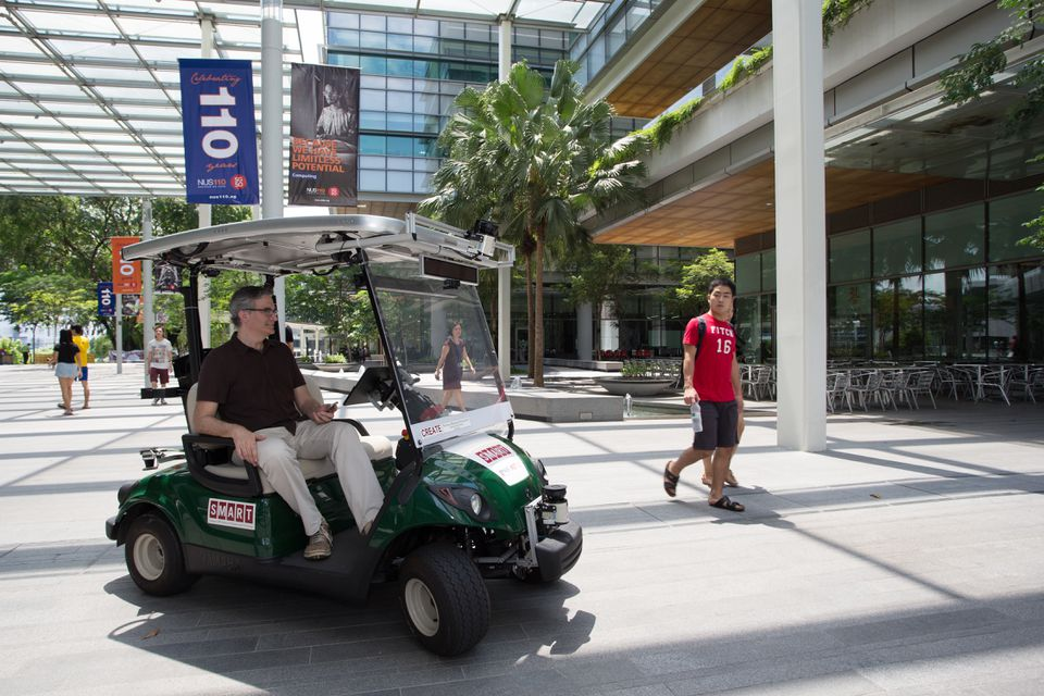 Stoking the curiosity of pedestrians, reporter Neil Swidey rides in a self-driving cart around Singapore's Campus for Research Excellence and Technological Enterprise.