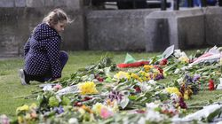 A child looked at flowers outside of Windsor Castle in Windsor, England after the announcement regarding the death of Britain's Prince Philip on Friday.