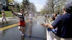 Joe Verdone (right) offered cooling relief with his garden hose for runners climbing Heartbreak Hill in Newton during the 2012 Marathon.