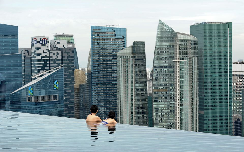 Visitors look at a view of the city skyline from the rooftop pool of the Marina Bay Sands resort hotel in Singapore on May 20, 2014.