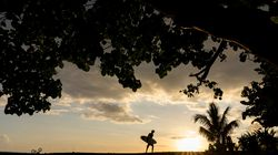 A surfer holds a board at the Orofara surfing spot near Mahina, on April 30, 2020.