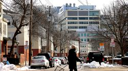 A woman walked by the Washington Elms Housing Development in Cambridge, which sits next to high-rise towers in Kendall Square.