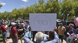 In this May 25 file photo, a man holds up a sign against critical race theory during a protest outside a Washoe County School District board meeting in Reno, Nev.