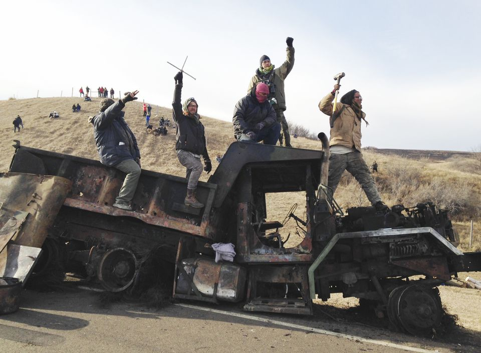Protesters against the Dakota Access oil pipeline stood on a burned-out truck near Cannon Ball, N.D., Monday. They had removed the truck from a long-closed bridge on Sunday on a state highway near their camp in southern North Dakota.