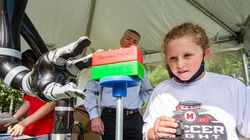 Maura Eckler, 9, uses a robotic commercial arm to move blocks in an interactive display at the Robot Block Party put on by MassRobotics in Boston on Oct. 2.