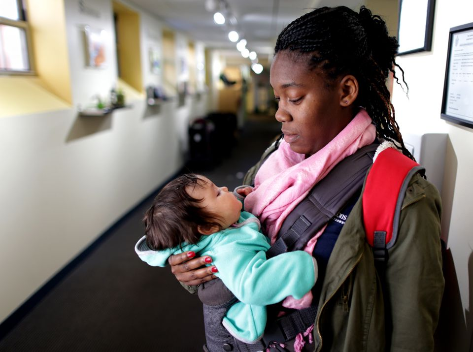 Infant teacher Victoria Jones holds baby Katherine at the Bright Horizons Day-Care center in Watertown.