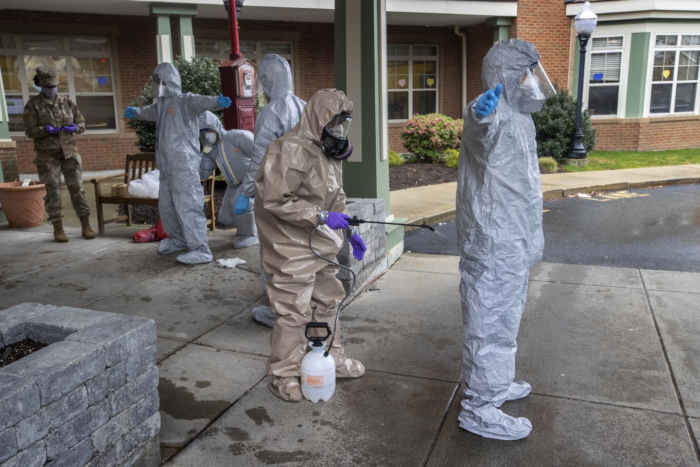 Members of the Massachusetts National Guard remove their hazmat suits after leaving Alliance Health at Marina Bay. The National Guard was deployed to Quincy to assist nursing homes with COVID-19 testing.
