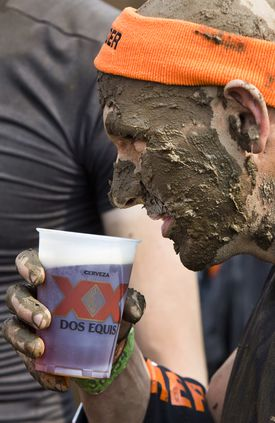 A Tough Mudder competitor gets a free beer after completing the obstacle course.