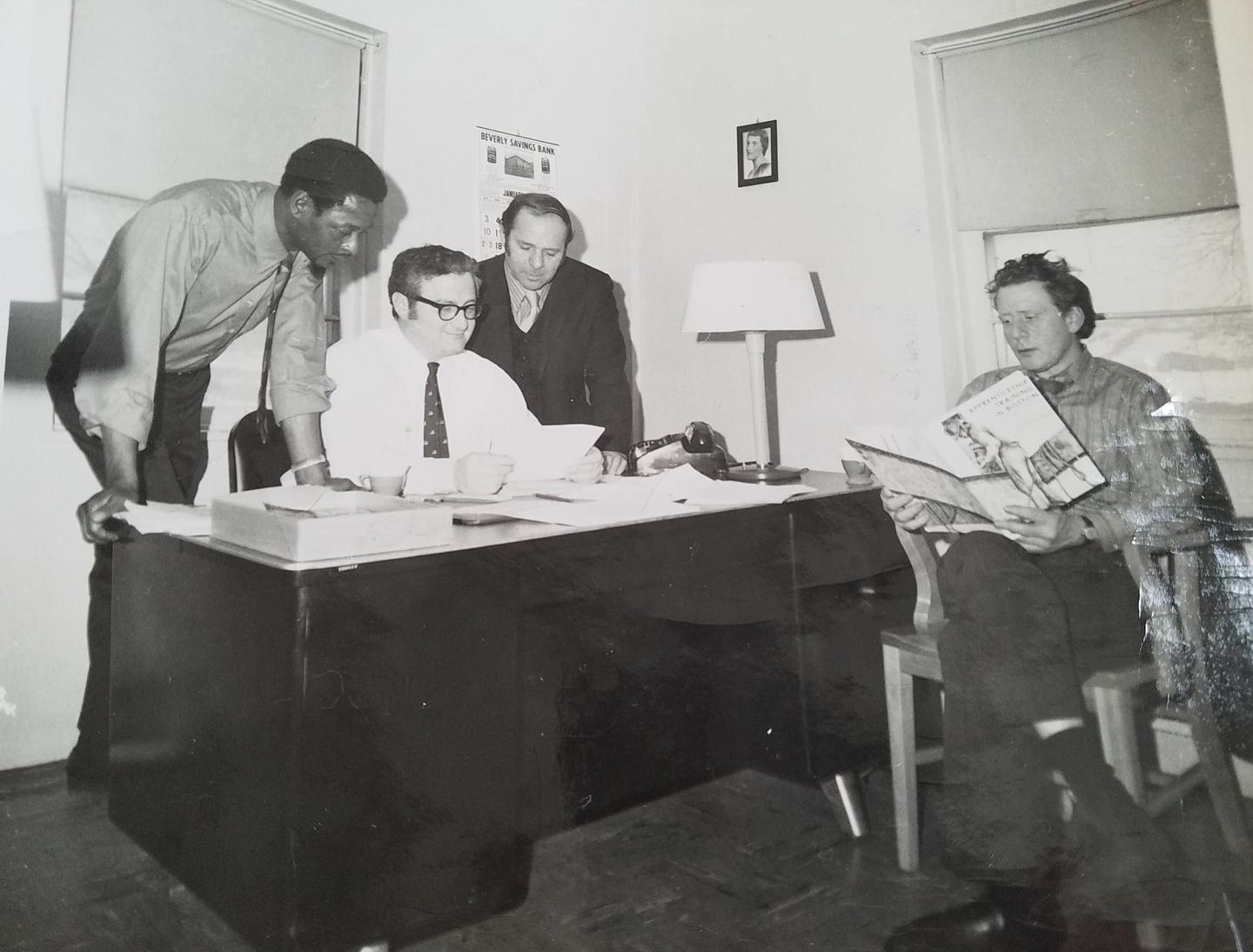 Bert Fliegel (seated at desk), director of Columbia Point Health Center, and his co-workers advocated for better health care for residents, circa 1972.