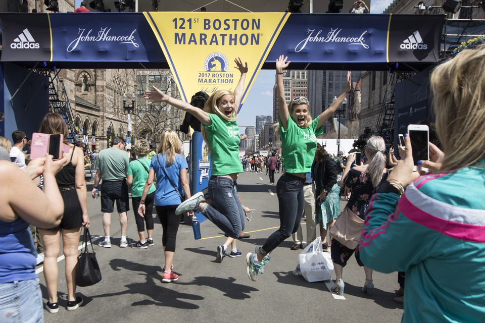 Two women jumped for a photograph at the finish line of the Boston Marathon on Saturday.