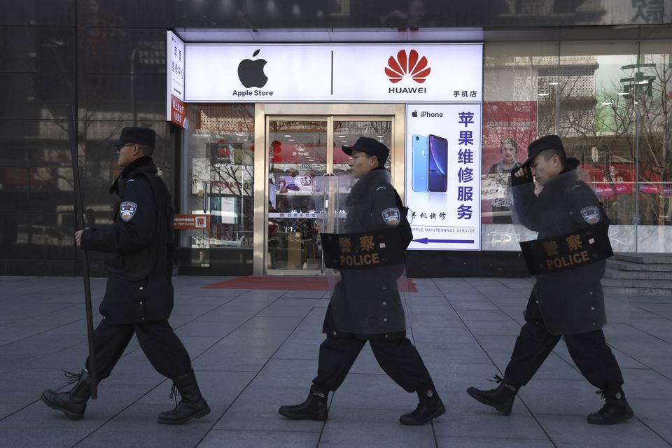 Security guards march past a shop selling Apple and Huawei phones in Beijing, China, March 6.