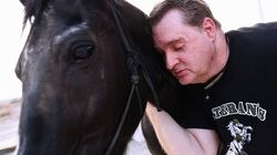 US Army veteran Daryn LaVoie, who is blind, shares a moment with horse Riley during a program pairing horses with veterans, on July 11 in Indio, Calif. LaVoie, a combat veteran, served during Operation Desert Storm from 1993 to1997 and suffered from post-traumatic stress disorder after his return home. He attempted to commit suicide in 2017 with his gun; the bullet severed both his optic nerves rendering him blind.