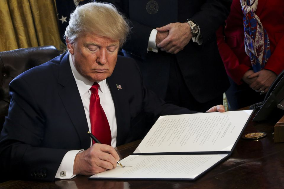 President Donald Trump signed an executive order in the Oval Office of the White House Friday.