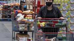 Shoppers wearing protective masks push shopping carts inside a Costco store in San Francisco on March 3.