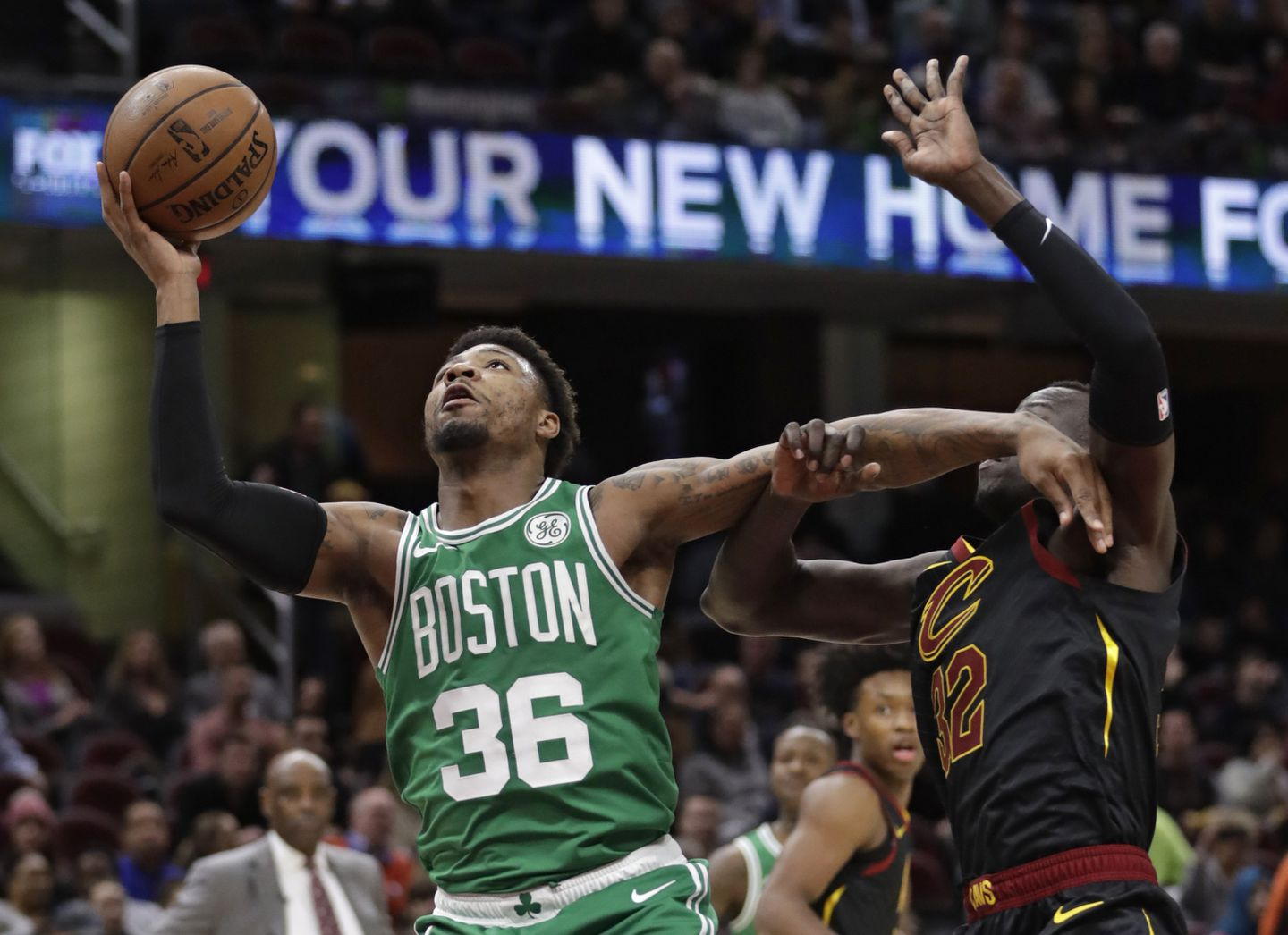 0c6fe9a9bb1 Celtics guard Marcus Smart keeps Deng Adel at arm s length to score on a  layup Tuesday