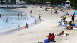 People sit on Waikiki Beach in Honolulu. Hawaii's COVID-19 case counts and hospitalizations have declined to the point where the islands are ready to welcome travelers once again, the governor said Tuesday, Oct. 19.