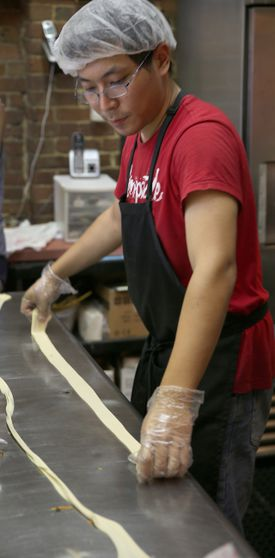 Yan Wang with hand pulled noodles at Gene's Chinese Flatbread Cafe.