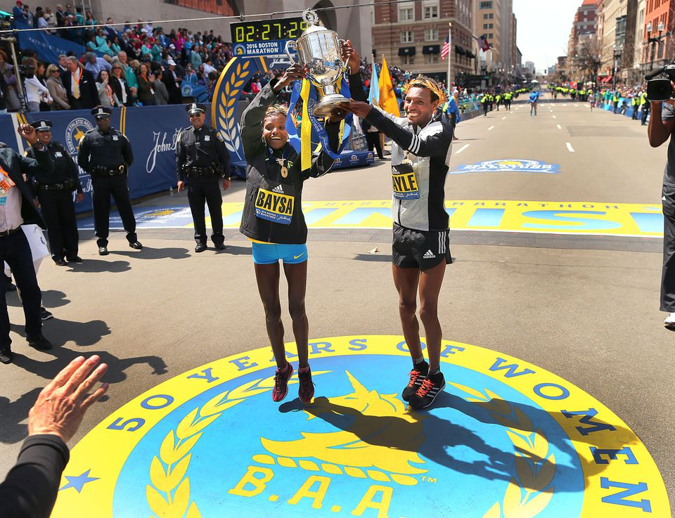 Astede Baysa and Lemi Berhanu Hayle jumped as they held a trophy at the finish line.