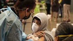 A student looks back at his mother as he is vaccinated at a school-based COVID-19 vaccination clinic for students 12 and older in San Pedro, Calif. California health officials are making plans to begin giving booster shots for older people along with vaccinations for kids under 12.