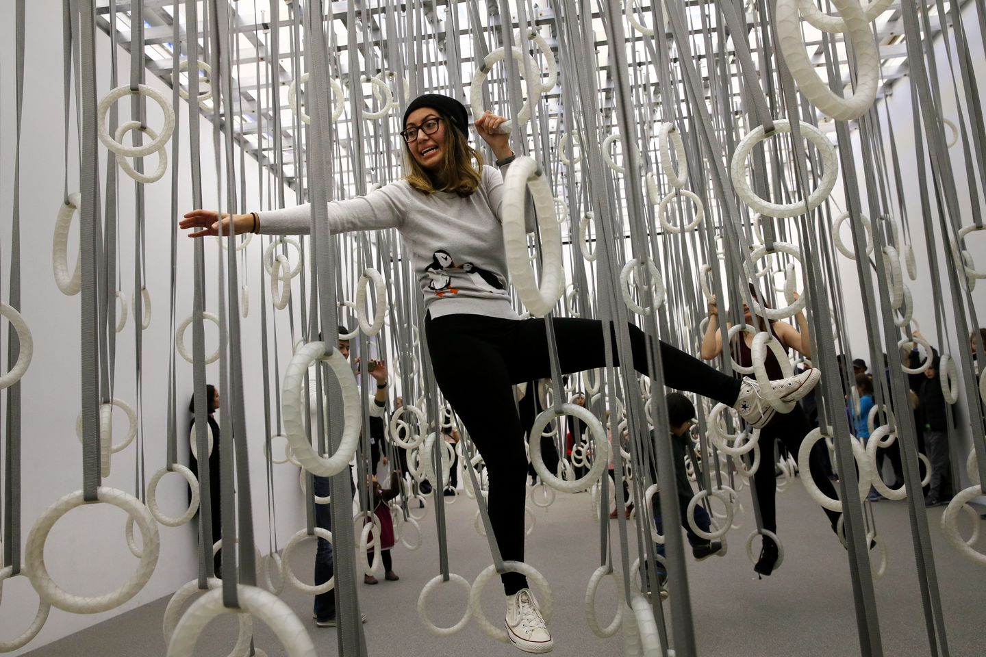 "Paula Suarez, of Malden, uses rings to cross the room in ""The Fact of Matter"" while visiting ""William Forsythe: Choreographic Objects"" at the Institute of Contemporary Art."