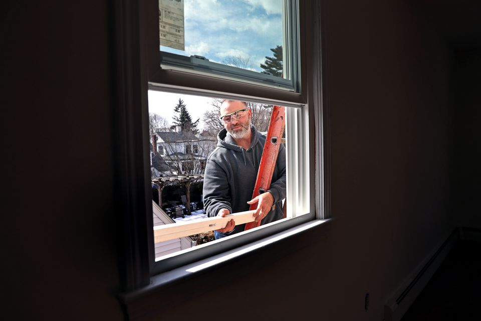 Shawn Young, who teaches home improvement classes at Keefe Tech, installed a window recently in a Waltham home.