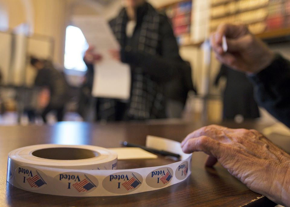 Rae Lunam, of Boston, handed out stickers to voters for the 2016 US presidential election at the polling location at the Boston Public Library.