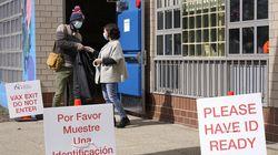 School bus driver John Sullivan (left) accepts a sticker from volunteer Colleen McNamara as he departs a Boston Public Schools vaccination clinic on March 14.