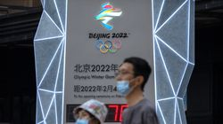 People wearing face masks to protect against COVID-19 walk past a display showing a countdown clock to the 2022 Winter Olympics in Beijing, Wednesday, Aug. 18, 2021.