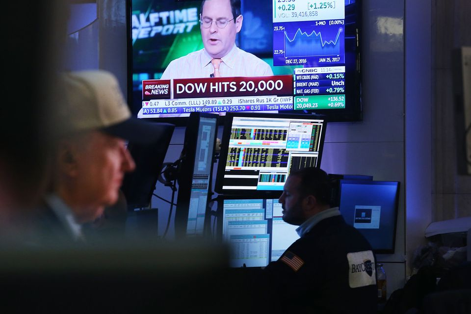 Traders worked on the floor of the New York Stock Exchange in late morning trading after the Dow Jones industrial average crossed the 20,000 mark for the first time.