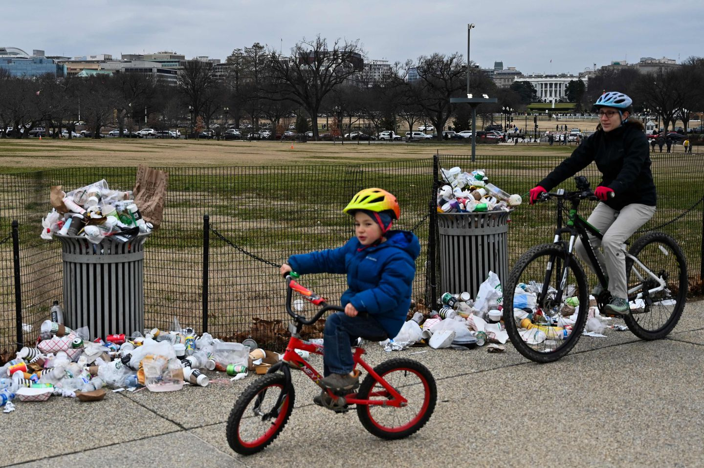 The White House was seen in the background as people biked past trash uncollected on the National Mall.