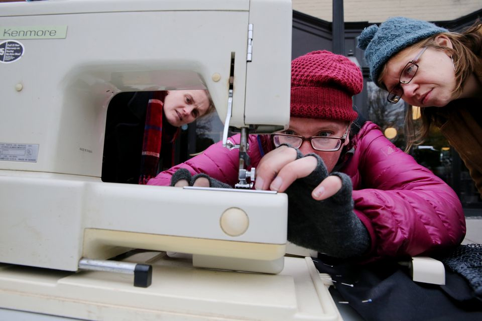 Christina Lively, Dina Gjertsen, and Erin Geno examine a sewing machine at the Fixer Fair in Somerville.