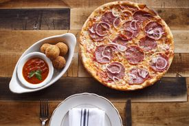 Arancini (left) are filled with creamy fontina and mascarpone, and the La Motta thin crust pizza features soppressata and red onion.