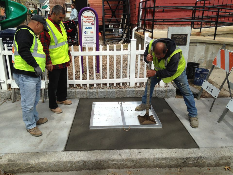 Crew of Fred DeRoma & Son, contractors with the City of Cambridge, apply the Cambridge Poetry Program test stamp in freshly poured concrete on the sidewalk in front of Cambridge Community Center on April 29, 2015.