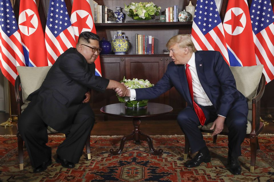 North Korea leader Kim Jong Un, left, and US President Trump shook hands during their first meeting at the Capella resort on Sentosa Island in Singapore. on June 12, 2018.
