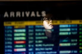 A woman is reflected in the arrivals board at Logan airport.