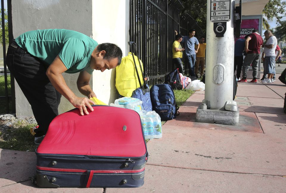 Leonel Geronimo stuffed food into his suitcase as he and others waited for a bus ahead of Hurricane Irma in Miami Beach.