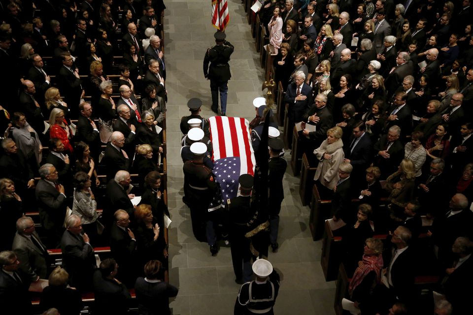 The flag-draped casket of former President George H.W. Bush is carried by a joint services military honor guard into St. Martin's Episcopal Church Thursday in Houston.