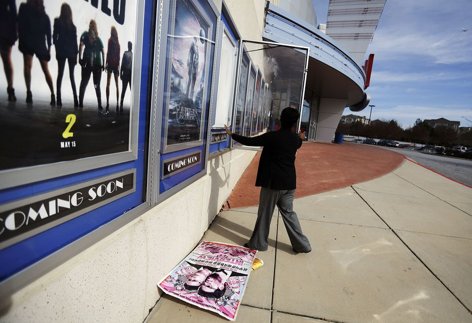 """A poster for the movie """"The Interview"""" is pulled from a display case by a worker at a Carmike Cinemas movie theater in Atlanta."""