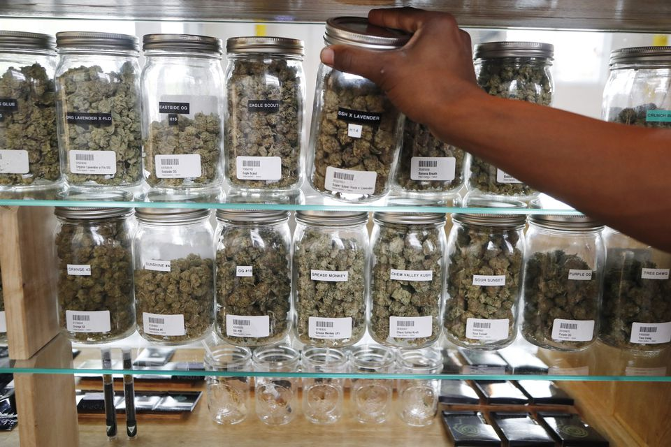 A clerk reaches for a container of marijuana buds for a customer at Utopia Gardens, a medical marijuana dispensary, in Detroit.