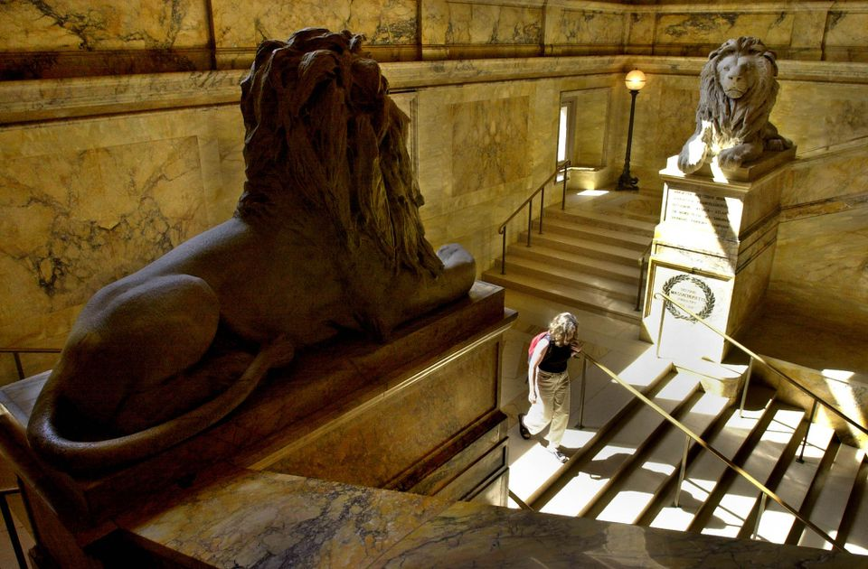 A visitor to the Boston Public Library walks down a stairway between two giant lions made of Italian marble donated by veterans of the Civil War.