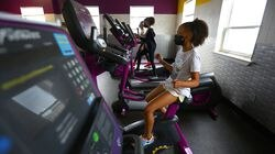 Delaney (foreground), 8, Aiyana, 10, and Laila, 10, used the exercise machines at the Paul R. McLaughlin Youth Center of the Boys and Girls Clubs of Dorchester. Masks will continue to be required indoors this summer, though they can come off outside.