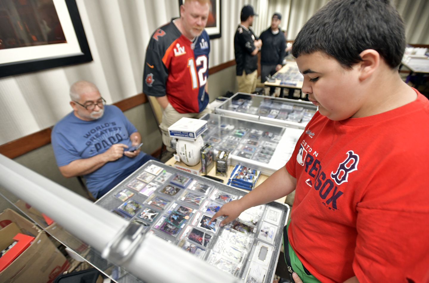 Davie Baia, 13, browses the table of father-and-son team WIlfred Bouchard of Fall River and Gregory Bouchard of Seekonk at the weekly Woburn Sportscard Show.