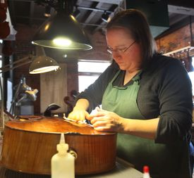 Carriage House Violins luthier Jess Fox tending to a cello.