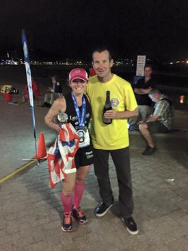 Becca Pizzi won the final women's race in 4:08:51 hours. She stood at the finish line with event director Richard Donovan.